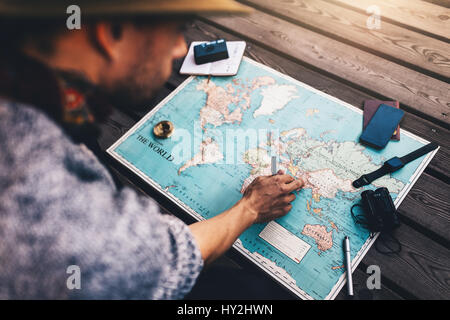 Tourist pointing at India on world map surrounded with binoculars, compass and other travel accessories. Man looking - Stock Photo