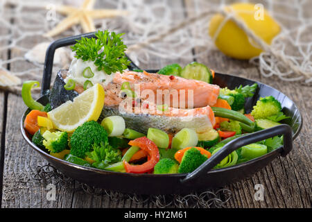 Tasty fried and grilled salmon steak on mixed colorful vegetables served in a frying pan,  lemons and a fishing - Stock Photo