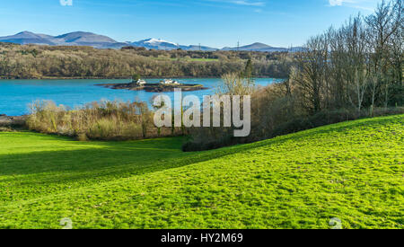 A view across the Menai Strait from a vantage point on Anglesey, with the Snowdonia mountains in the background - Stock Photo