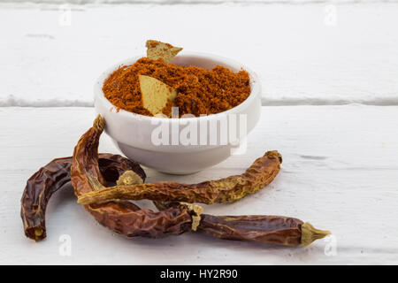 Red Chili pepper powder in white bowl with dried chili peppers on white table - Stock Photo