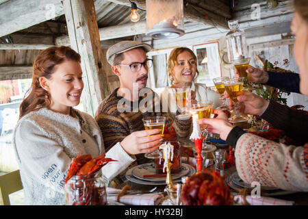 Sweden, People raising toast during crayfish party - Stock Photo