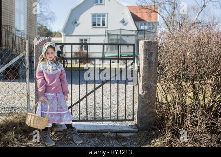 Sweden, Girl (4-5) dressed up as Easter witch with Easter basket standing by gate - Stock Photo