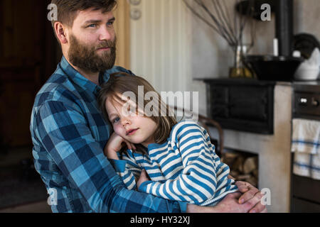 Sweden, Portrait of father embracing daughter (4-5) in kitchen - Stock Photo