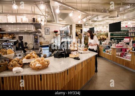 Sweden, Woman choosing food in bakery - Stock Photo