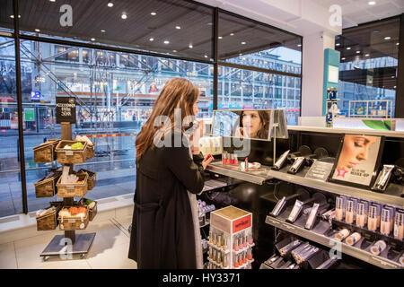 Sweden, Woman testing lipstick in perfumery - Stock Photo