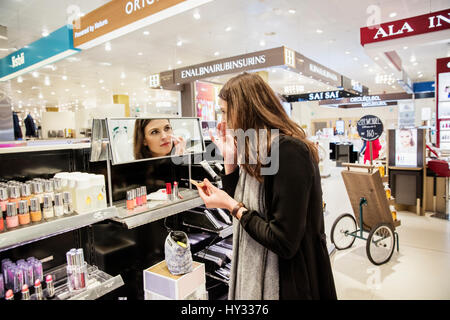 Sweden, Woman testing foundation in perfumery - Stock Photo