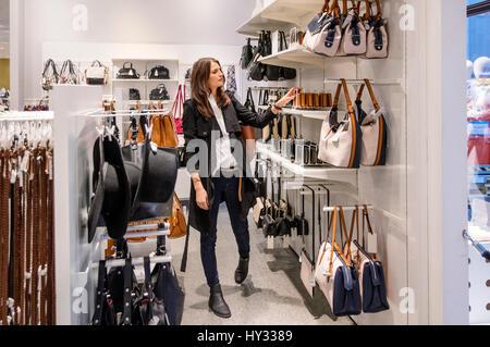 Sweden, Woman choosing purse in shop - Stock Photo