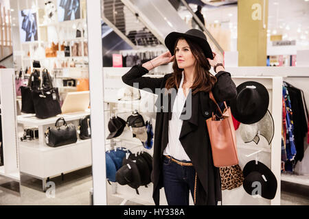 Sweden, Woman choosing hat in shop - Stock Photo