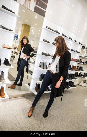 Sweden, Woman choosing shoes in store - Stock Photo