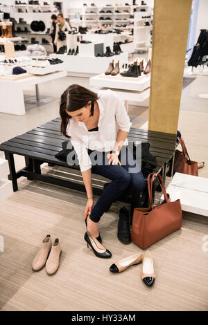 Sweden, Woman trying on shoes in store - Stock Photo