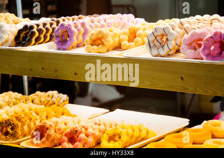 Display of delicious pastries in a bakery with assorted glazed colorful and tasty doughnuts or donuts with sprinkles - Stock Photo