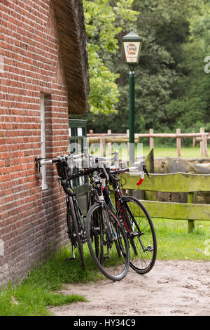 Three touring bicycles parked against an old brick wall with a little window in France, Europe. - Stock Photo
