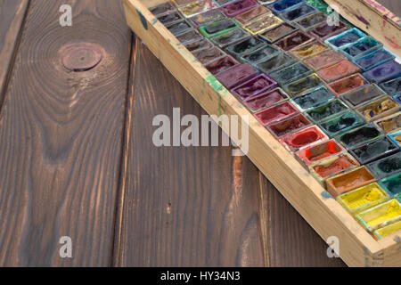 Box with watercolors and brushes on wooden surface - Stock Photo