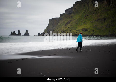 Iceland, Sudurland, Vik i Myrdal, Hiker walking on black sand beach at feet of cliff - Stock Photo