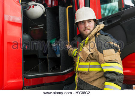 Sweden, Sodermanland, Firefighter standing in front of fire truck - Stock Photo