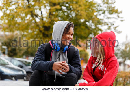 Sweden, Sodermanland, Jarna, Girls (12-13) in hoodies smiling at each other - Stock Photo