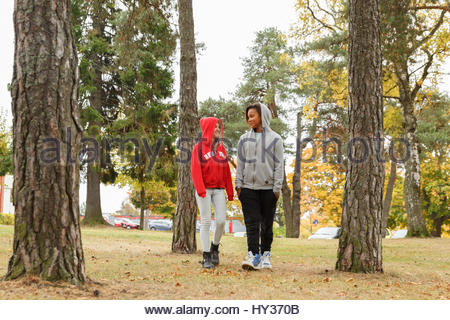 Sweden, Sodermanland, Jarna, Girls (12-13) with hoods on chatting while walking among trees - Stock Photo
