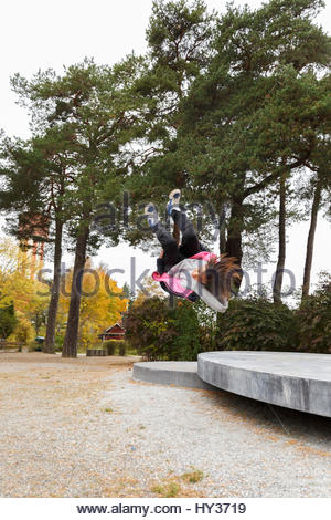 Sweden, Sodermanland, Jarna, Girl (12-13) doing somersault in park - Stock Photo