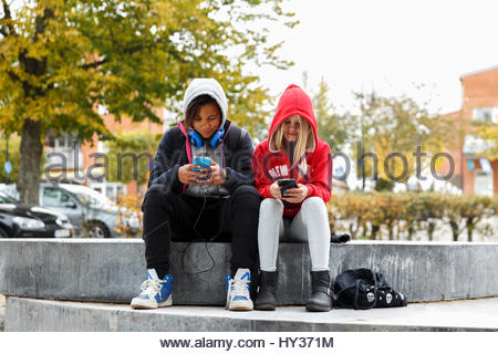 Sweden, Sodermanland, Jarna, Girls (12-13) in hoodies sitting on wall and using smart phones - Stock Photo