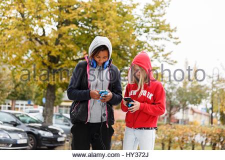 Sweden, Sodermanland, Jarna, Girls (12-13) with hoods on using smart phones - Stock Photo