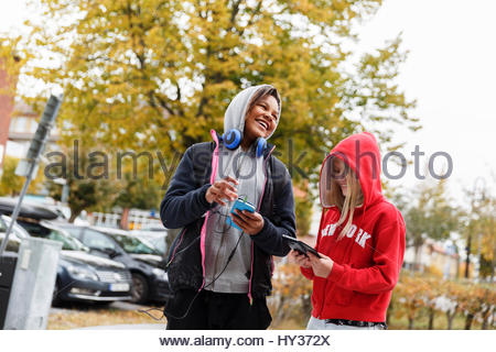 Sweden, Sodermanland, Jarna, Girls (12-13) with hoods on using smart phones and laughing - Stock Photo
