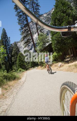 USA, California, Yosemite, Boy (14-15) riding bicycles on mountain road - Stock Photo