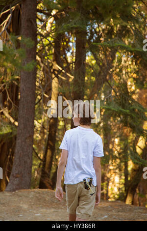 USA, California, Yosemite, Boy (14-15) walking through forest with catapult toy in pocket - Stock Photo