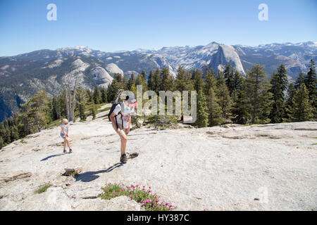 USA, California, Yosemite, Girl (12-13) and boy (14-15) walking up high mountain with view at Sentinel Dome and - Stock Photo