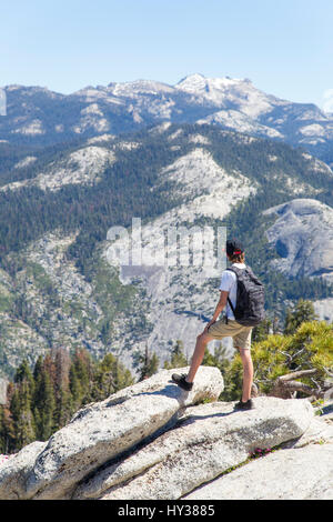 USA, California, Yosemite, Boy (14-15) looking at view with Sentinel Dome and Yosemite Falls - Stock Photo