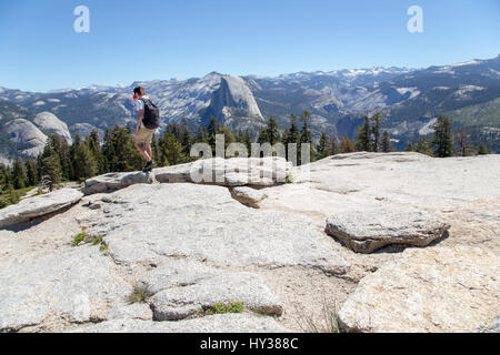 USA, California, Yosemite, Boy (14-15) during mountain trip, Sentinel Dome and Yosemite Falls in background - Stock Photo