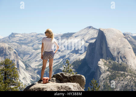 USA, California, Yosemite, Girl (12-13) looking at view with Sentinel Dome and Yosemite Falls - Stock Photo