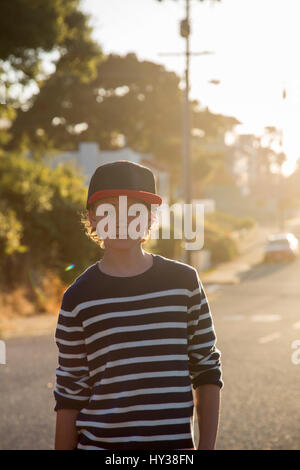 USA, California, Pacific Grove, Portrait of boy (14-15) standing in street at sunset - Stock Photo