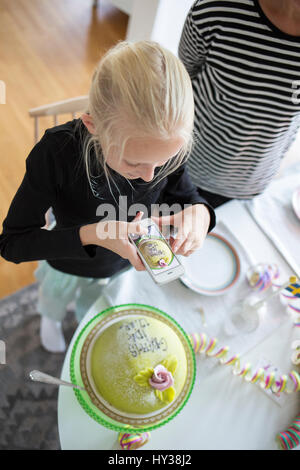 Sweden, Girl (12-13) photographing birthday cake with cell phone - Stock Photo