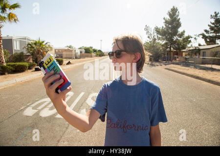 USA, California, Boy (14-15) taking selfie in street - Stock Photo