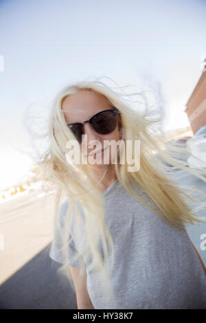 USA, California, Portrait of blonde girl (12-13) wearing sunglasses - Stock Photo
