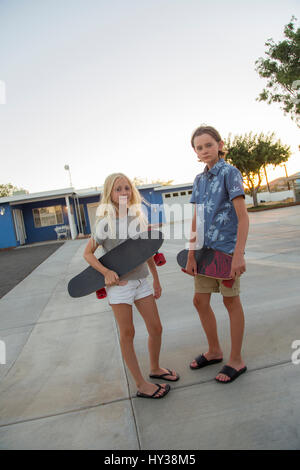 USA, California, Boy (14-15) and girl (12-13) with skateboards in street - Stock Photo