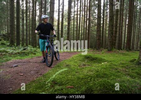 Sweden, Vastergotland, Lerum, Mature man with bicycle in forest - Stock Photo