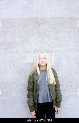 Sweden, Portrait of girl (12-13) standing against concrete wall - Stock Photo