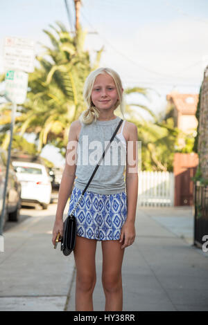 USA, California, San Diego, Portrait of girl (12-13) standing in street with palm tree in background Stock Photo