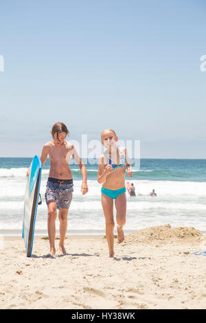 USA, California, San Diego, Boy (14-15) with surfboard and girl (12-13) walking on beach - Stock Photo