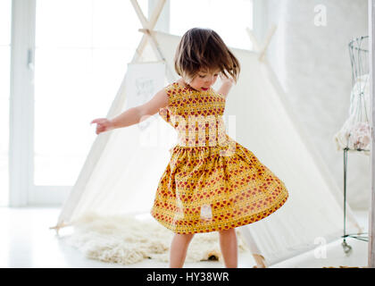 Sweden, Girl (4-5) dancing next to tent at home - Stock Photo