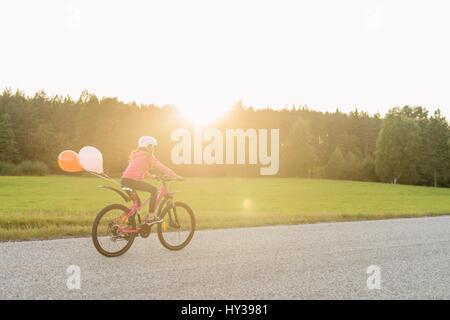 Sweden, Vastmanland, Hallefors, Bergslagen, Girl (10-11) riding bicycle at sunset - Stock Photo