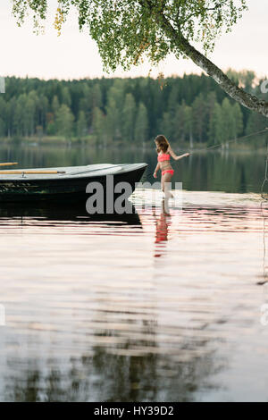 Sweden, Vastmanland, Hallefors, Bergslagen, Girl ( 8-9) standing in lake - Stock Photo