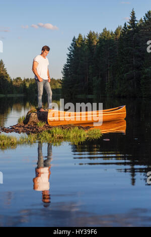 Sweden, Vastmanland, Hallefors, Bergslagen, Man standing on boulder in middle of lake - Stock Photo
