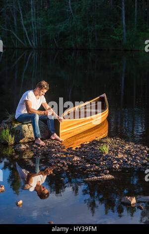 Sweden, Vastmanland, Hallefors, Bergslagen, Man sitting on boulder in middle of lake - Stock Photo