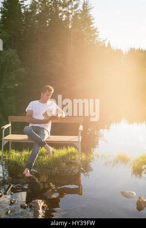 Sweden, Vastmanland, Hallefors, Bergslagen, Man sitting on bench in middle of lake - Stock Photo