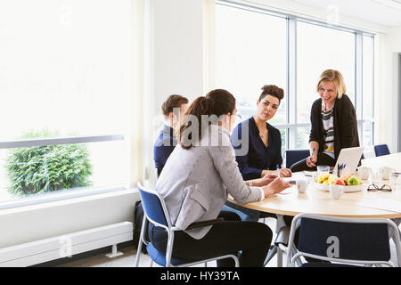 Sweden, Young people sharing ideas during board meeting - Stock Photo