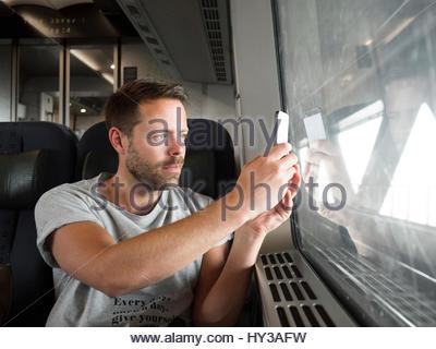 Sweden, Skane, Man taking photograph through train window - Stock Photo