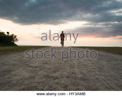 Sweden, Skane, Malmo, Woman cycling on dirt road against moody sky - Stock Photo