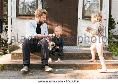 Sweden, Skane Father sitting on steps and feeding son (2-3) - Stock Photo